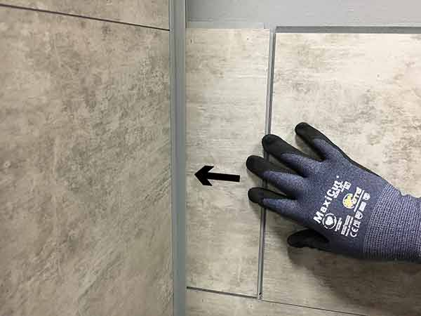 Push tile into corner trim channel until it can lay flat on the substrate